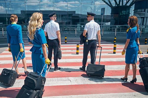 Piloten en stewardessen lopen naar luchthaven in bedrijfskleding